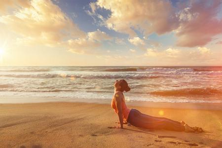 Yoga outdoors on beach - woman practices Ashtanga Vinyasa yoga Surya Namaskar Sun Salutation asana Urdhva Mukha Svanasana - upward facing dog pose on sunset. With light leak and lens flare