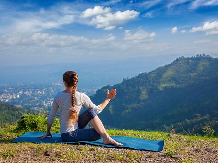 Hatha yoga outdoors - sporty fit woman doing yoga asana Parivrtta Marichyasana (or ardha matsyendrasana) -  seated spinal twist outdoors in mountains in the  morning