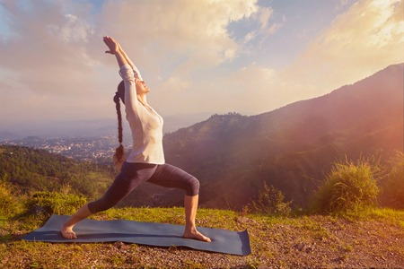 warrior pose: Yoga outdoors - sporty fit woman doing yoga asana Virabhadrasana 1 - Warrior pose posture outdoors in Himalayas mountains in the morning