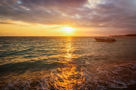 sunsets: Calm ocean with boat during tropical sunrise