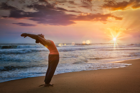 hasta: Young sporty fit man doing yoga Sun salutation Surya Namaskar pose Hasta Uttanasana on tropical beach on sunset. With lens flare