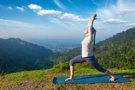 yogic: Yoga outdoors - sporty fit woman doing yoga asana Virabhadrasana 1 - Warrior pose posture outdoors in Himalayas mountains in the morning
