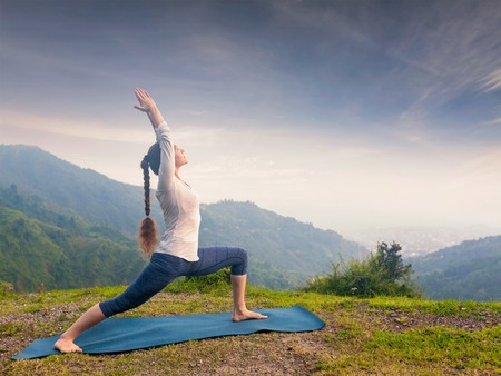 ashtanga: Yoga outdoors - sporty fit woman doing Ashtanga Vinyasa Yoga asana Virabhadrasana 1 Warrior pose posture in HImalayas mountains on sunset