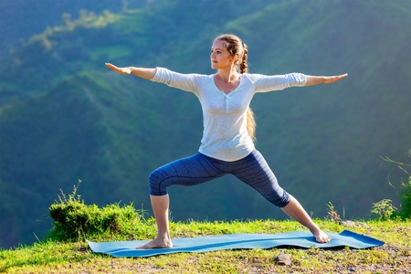 warrior pose: Yoga outdoors - sporty fit woman doing yoga asana Virabhadrasana 2 - Warrior pose posture outdoors in Himalayas mountains in the morning