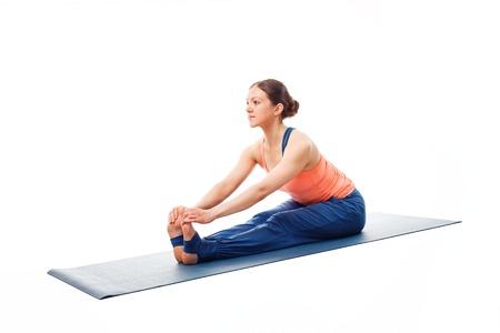 beginner: Woman doing Ashtanga Vinyasa Yoga asana Paschimottanasana - seated forward bend pose beginner variation isolated on white background