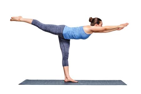 Beautiful sporty fit woman practices yoga asana Virabhadrasana 3 - warrior 3 pose isolated on white Stock Photo