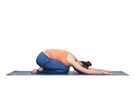 yogini: Beautiful sporty fit yogini woman practices yoga asana balasana (childs pose) - resting pose or counter asana for many asanas in studio isolated on white Stock Photo