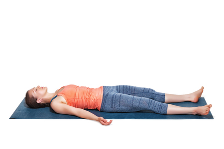 position: Beautiful sporty fit woman relaxes in yoga asana Savasana - corpse pose in studio isolated on white