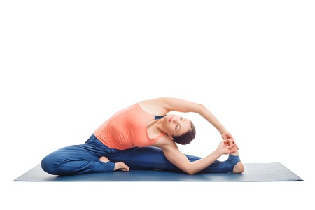 revolved: Beautiful sporty fit yogini woman practices yoga asana parivrtta janu sirsasana - revolved head-to-knee pose isolated on white background Stock Photo