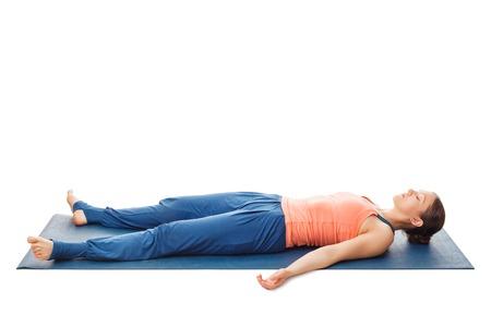 La donna si distende in asana yoga savasana - cadavere pongono isolato su bianco