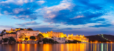 romantic sky: Panorama of famous romantic luxury Rajasthan indian tourist landmark - Udaipur City Palace in the evening twilight with dramatic sky - panoramic view. Udaipur, India