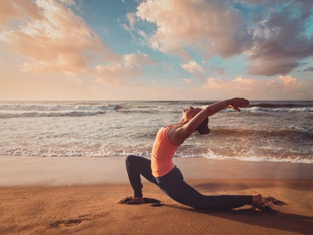 Vintage retro effect filtered hipster style image of Yoga outdoors - sporty fit woman practices yoga Anjaneyasana - low crescent lunge pose outdoors at beach on sunset Stock Photo