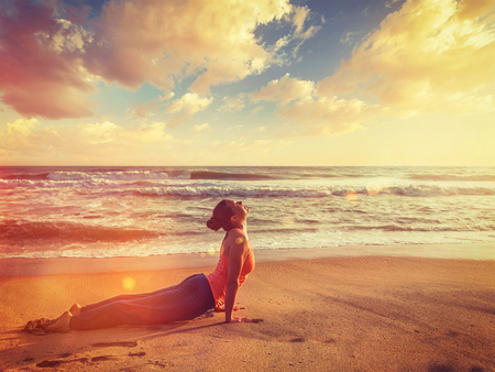 Vintage retro effect filtered hipster style image of Yoga outdoors on beach - woman practices Ashtanga Vinyasa yoga Surya Namaskar Sun Salutation asana Urdhva Mukha Svanasana - upward facing dog pose on sunset. With light leak and lens flare