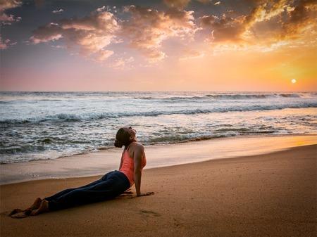 dog pose: Yoga outdoors - woman doing Ashtanga Vinyasa yoga Surya Namaskar Sun Salutation asana Urdhva Mukha Svanasana - upward facing dog pose on sunset on beach. Vintage retro effect filtered hipster style image