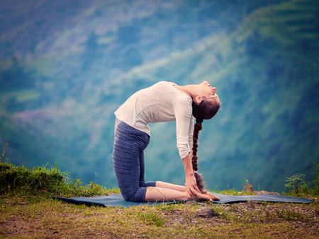 Yoga - outdoors  young beautiful slender woman yoga instructor doing camel pose Ustrasana asana exercise outdoors. Vintage retro effect filtered hipster style image.