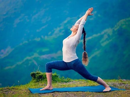 Yoga outdoors - sporty fit woman doing Ashtanga Vinyasa Yoga asana Virabhadrasana 1 Warrior pose posture in HImalayas mountains. Vintage retro effect filtered hipster style image. Stock Photo