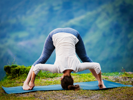 ashtanga: Yoga exercise outdoors -  woman doing Ashtanga Vinyasa Yoga asana Prasarita padottanasana  D - wide legged forward bend pose outdoors. Vintage retro effect filtered hipster style image.