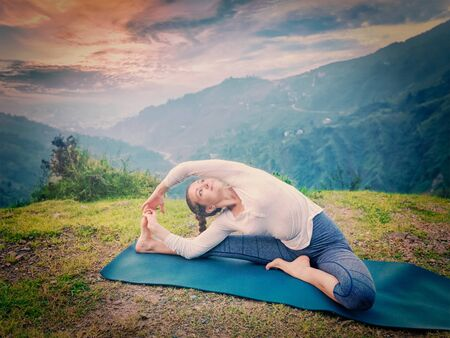 Yoga outdoors - young sporty fit woman doing Hatha Yoga asana janu sirsasana - Revolved Head-to-Knee Pose - in. Vintage retro effect filtered hipster style image. Stock Photo