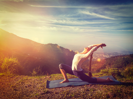 Yoga outdoors - sporty fit woman practices yoga Anjaneyasana - low crescent lunge pose outdoors in mountains in morning. With light leak and lens flare. Vintage retro effect filtered hipster style image.
