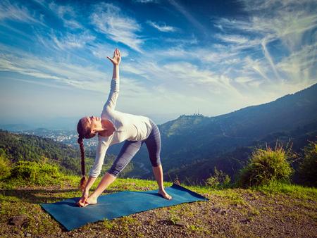 Woman doing Ashtanga Vinyasa yoga asana Utthita trikonasana - extended triangle pose outdoors in mountains in the morning. Vintage retro effect filtered hipster style image.
