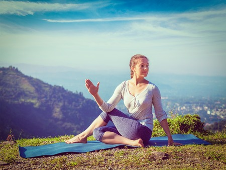 Yoga exercise outdoors - woman doing Ardha matsyendrasana asana - half spinal twist pose mountains in Himalayas in India in the morning. Vintage retro effect filtered hipster style image.