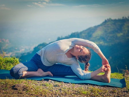 janu: Yoga outdoors - young sporty fit woman doing Hatha Yoga asana parivritta janu sirsasana - Revolved Head-to-Knee Pose - in mountains in the morning. Vintage retro effect filtered hipster style image. Stock Photo