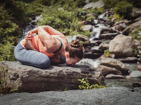 Vintage retro effect filtered hipster style image of Young sporty fit woman doing yoga - meditating in Baddha Padmasana (Bound Lotus Pose) outdoors at tropical waterfall