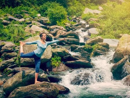 nataraja: Yoga outdoors - woman doing yoga asana Natarajasana - Lord of the dance balance pose outdoors at waterfall in Himalayas. Vintage retro effect filtered hipster style image.