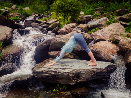 yogic: Young sporty fit woman doing yoga asana Adho mukha svanasana - downward facing dog - at tropical waterfall. Vintage retro effect filtered hipster style image.