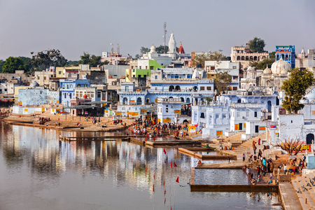 a bathing place: PUSHKAR, INDIA - NOVEMBER 20, 2012: Hindu devotees pilgrims bathing in sacred Puskhar lake (Sagar) on ghats of  Pushkar, Rajasthan, India. Pushkar is holy city for Hinduists and famous for many Hindu temples
