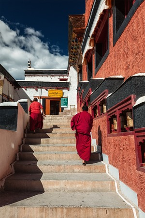 ladakh: THIKSEY, INDIA - SEPTEMBER 13, 2012: Young Buddhist monks walking on stairs along prayer wheels in Thiksey gompa Tibetan Buddhist monastery, Ladakh, India Editorial