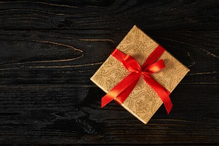 gift ribbon: Gift birthday Christmas present concept - gift box with red ribbon on dark wooden background
