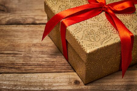 Gift present birthday Christmas concept - gift box with red ribbon on wooden background close up