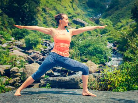 Yoga outdoors - sporty fit woman doing Ashtanga Vinyasa Yoga asana Virabhadrasana 2 Warrior pose posture at tropical waterfall. Vintage retro effect filtered hipster style image.