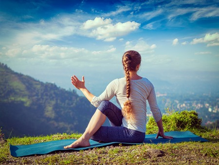 Hatha yoga outdoors - sporty fit woman doing yoga asana Parivrtta Marichyasana (or ardha matsyendrasana) -  seated spinal twist outdoors in mountains in the  morning. Vintage retro effect filtered hipster style image.