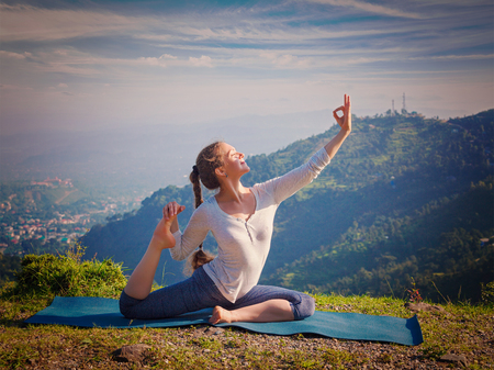 pada: Yoga outdoors - young sporty fit woman doing stretching yoga asana Eka pada rajakapotasana - one-legged king pigeon pose in Himalayas mountains, India. Vintage retro effect filtered hipster style image.