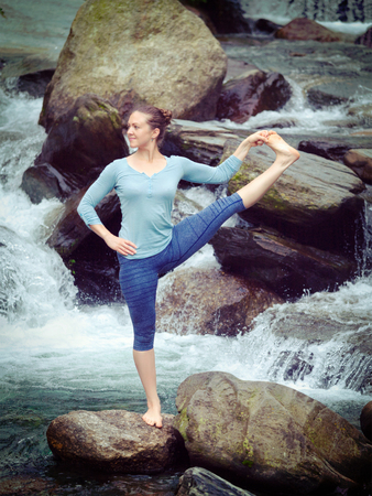 hasta: Yoga outdoors - woman doing Ashtanga Vinyasa Yoga balance asana Utthita Hasta Padangushthasana - Extended Hand-To-Big-Toe Pose position posture outdoors at waterfall. Vintage retro effect filtered hipster style image. Stock Photo