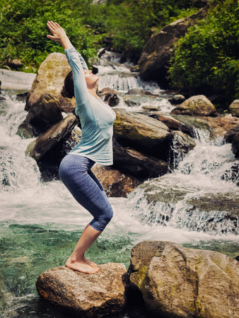 yogic: Vintage retro effect hipster style image of sporty fit woman doing yoga asana Utkatasana (chair pose) outdoors at tropical waterfall standing on stone
