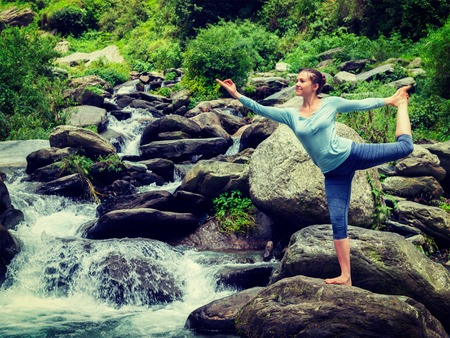 yogic: Woman doing yoga asana Natarajasana - Lord of the dance pose outdoors at waterfall in Himalayas. Vintage retro effect filtered hipster style image. Stock Photo