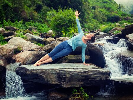 yogic: Yoga outdoors - beautiful sporty fit woman doing yoga asana Vasisthasana - side plank pose at tropical waterfall. Vintage retro effect filtered hipster style image.
