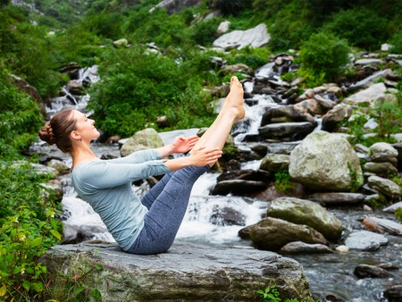 Yoga outdoors - young sporty fit woman doing Ashtanga Vinyasa Yoga asana Navasana - boat pose - in Himalayas at waterfall. Himachal Pradesh, India. Vintage retro effect filtered hipster style image. Stock Photo