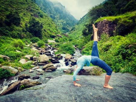 Yoga outdooors - woman doing yoga asana eka pada urdva dhanurasana Upward Bow Pose back benkd outdoors at waterfall in Himalayas. Vintage retro effect filtered hipster style image.