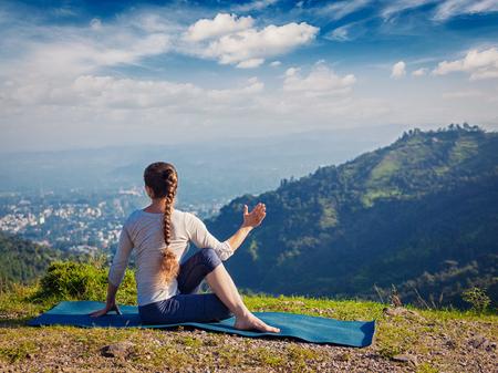 Hatha yoga outdoors - woman doing yoga asana Parivrtta Marichyasana (or ardha matsyendrasana) - seated spinal twist outdoors in mountains in morning. Vintage retro effect hipster style image.