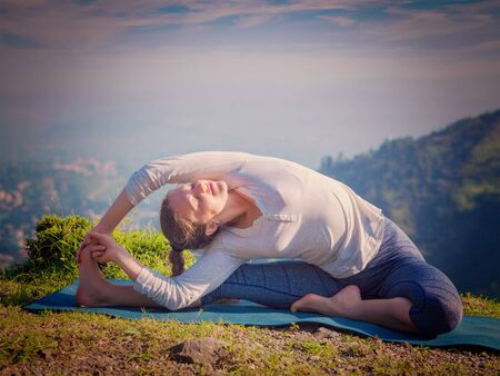 Yoga outdoors - young sporty fit woman doing Hatha Yoga asana parivritta janu sirsasana - Revolved Head-to-Knee Pose - in mountains in the morning. Vintage retro effect filtered hipster style image. Stock Photo