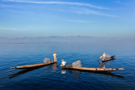 distinctive: Myanmar travel attraction landmark - Traditional Burmese fishermen with fishing nets on boats at Inle lake in Myanmar famous for their distinctive one legged rowing style Stock Photo
