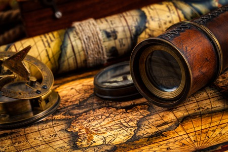 Travel geography navigation concept background - old vintage retro compass with sundial, spyglass on ancient world map Stock Photo