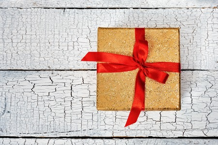 christmas present box: Gift birthday Christmas present concept - yellow gold gift box with red ribbon on white painted wooden background. Top view