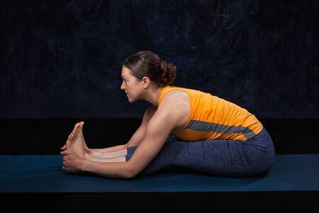 Woman doing Hatha yoga Ashtanga Vinyasa yoga asana Paschimottana