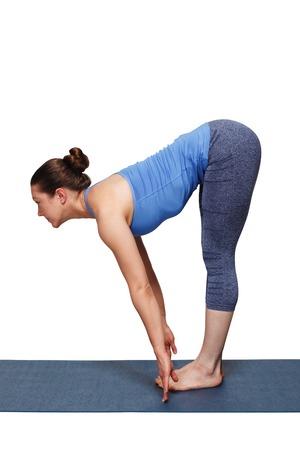 Woman doing yoga asana Uttanasana - standing forward bend Stock Photo