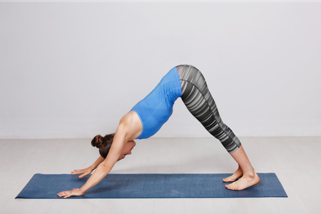Woman doing Ashtanga Vinyasa yoga asana Adhomukha svanasana Imagens
